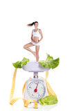 Healthy diet. A girl with perfect body on kitchen weights isolated on white Stock Photography