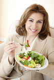 Healthy Diet. Young professional woman in business suite eating a healthy salad Royalty Free Stock Image