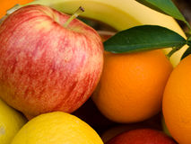 Healthy diet. Basket with fresh apples, oranges, lemons, and bananas Stock Photos