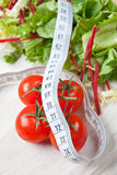 Healthy diet. Of tomatoes and salad with a tape measure Royalty Free Stock Image