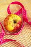 Healthy diet: apple and measuring tape. Apple annd measuring tape as elements for weight loss Stock Photo