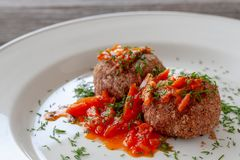 Bean meatballs with sweet pepper sauce on a white plate, decorated with herbs. stock image