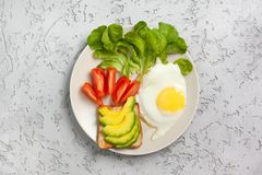 Healthy diet breakfast. Toast with slices of avocado, fried egg, tomatoes, watercress on a plate on a concrete background. view from above Royalty Free Stock Photos