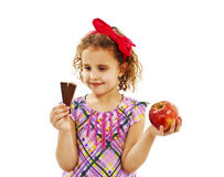 Little girl with apple and chocolate Stock Photo
