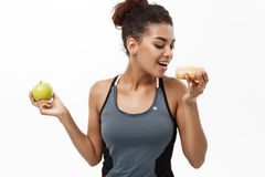 Healthy and diet concept - Beautiful sporty African American make a decision between donut and green apple. Isolated on. White background Stock Images
