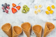 Healthy diet concept - fruits and frozen berries in ice cream cones on rustic background. Copy space Royalty Free Stock Photos
