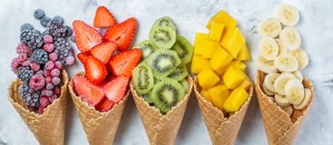 Healthy diet concept - fruits and frozen berries in ice cream cones on rustic background. Copy space Stock Photo