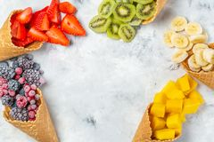 Healthy diet concept - fruits and frozen berries in ice cream cones on rustic background. Copy space Royalty Free Stock Image