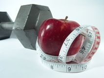 Healthy Diet & Exercise. High resolution digital photo of an apple and a measuring tape symbolize healthy diet and body weight control. Dumbbell represents stock photography