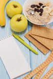 Healthy diet, fitness and weight loss concept, apple, notepad, pencil, measuring tape on the table. View from above. Healthy diet, fitness and weight loss Stock Image