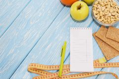 Healthy diet, fitness and weight loss concept, apple, notepad, pencil, measuring tape on the table. View from above. Healthy diet, fitness and weight loss Royalty Free Stock Image