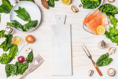 Healthy or diet food background with cutting board, organic spinach leaves, salmon, pan ,fork and cooking ingredients Stock Image