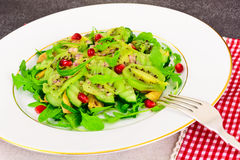 Healthy and diet food: Salad with arugula, avocado, kiwi, cucumb Royalty Free Stock Images