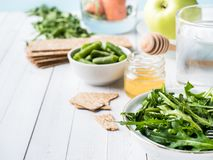 Healthy diet food on the table Arugula Green Beans Apple Water Honey Cracker Carrot Copy space. Healthy diet food on the table Arugula Green Beans Apple Water Stock Photography