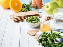 Healthy diet food on the table Arugula Green Beans Apple Water Honey Cracker Carrot Orange Copy space. Healthy diet food on the table Arugula Green Beans Apple Royalty Free Stock Image