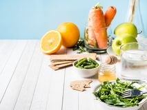 Healthy diet food on the table Arugula Green Beans Apple Water Honey Cracker Carrot Orange Copy space. Healthy diet food on the table Arugula Green Beans Apple Stock Photo