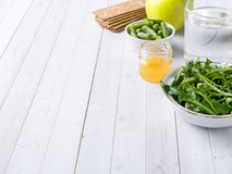 Healthy diet food on the table Arugula Green Beans Apple Water Honey Cracker.  Royalty Free Stock Photography