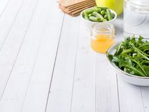 Healthy diet food on the table Arugula Green Beans Apple Water Honey Cracker.  Royalty Free Stock Images