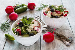 Healthy diet food: vegan vegetable salad with fresh cucumbers, radish, green onion, black olives, dill and feta cheese Stock Photo