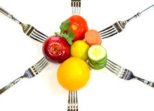 Healthy Diet. Food on a white background. apples, orange, green leaves, spinach, carrot, cucumber, tomato and lemon with fork Royalty Free Stock Image