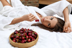 Healthy Diet Food For Woman's Health. Girl Eating Fruits On Bed Stock Image