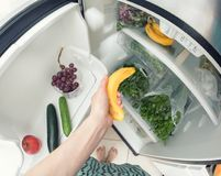 Healthy diet: A hand grabbing a banana from the open refrigerator full of greens. Celery, apple, grape and cucucmbers inside Royalty Free Stock Photos