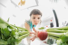 Healthy diet: A hand grabbing an apple from the open refrigerator full of greens. Healthy diet: A hand grabbing a banana from the open refrigerator full of Royalty Free Stock Images
