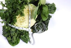 Healthy diet health foods with leafy green vegetables and tape measure. royalty free stock photo