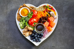 Healthy diet for heart and cardiovascular system. Healthy diet for the cardiovascular system with a heart-shaped plate of acai, lentils, soy sauce, ginger royalty free stock photos