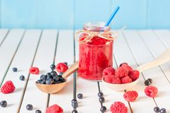 Healthy diet high dietary fiber breakfast with. Blueberries and raspberries in mason jar on aqua blue rural wooden background Stock Photography