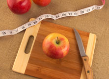 Healthy diet and nutrition for weight loss. Concept using apple and measuring tape Stock Photos