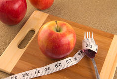 Healthy diet and nutrition for weight loss. Concept using apple and measuring tape Royalty Free Stock Images