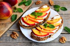 Rye bread sandwiches with soft cream cheese, nectarines, walnuts and mint on a serving plate and on a vintage wooden table. Healthy diet and nutrition for woman Royalty Free Stock Photos