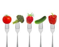 Healthy diet, organic food on forks with vegetables and berries. Royalty Free Stock Photos