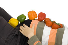 Healthy diet in pregnancy. Peppers and tomatoes are on a pregnant woman Royalty Free Stock Image