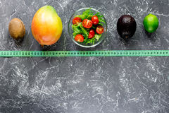 Healthy diet. Salad with fresh products and fruits mango, mangosteen, kiwi and measuring tape on stone table top view Royalty Free Stock Image
