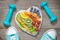 Healthy diet and sport concept with dumbbells trainers and food Stock Photography