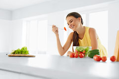 Healthy Diet. Woman Eating Vegetarian Salad. Healthy Eating, Foo. Healthy Diet. Beautiful Smiling Woman Eating Fresh Organic Vegetarian Salad In Modern Kitchen Stock Images
