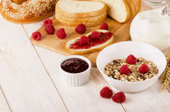 Healthy dietary breakfast with muesli, milk, fresh raspberries,. Jam and bun on a white wooden table and space for text Royalty Free Stock Images