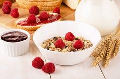 Healthy dietary breakfast with muesli, milk, fresh raspberries a. Healthy breakfast with muesli, milk, fresh raspberries, jam and bun on a wooden table Stock Photo