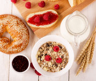 Healthy dietary breakfast with muesli, milk, fresh raspberries,. Jam and bun on a wooden table, view from above Stock Photo