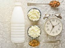 Healthy, dietary food. Morning breakfast. A bottle of yogurt. Bowls with cottage cheese, spoons with walnuts and raisins, alarm clock on a gray concrete table stock photos