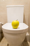 Healthy digestion. Toilet and an apple in the form of healthy food and good digestion Royalty Free Stock Image