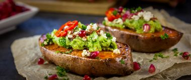 Healthy dinner - Baked sweet potatoes served with guacamole, feta cheese and pomegranate. On the white baking paper stock photos