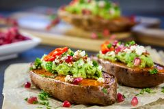 Healthy dinner - Baked sweet potatoes served with guacamole, feta cheese and pomegranate. On the white baking paper royalty free stock images