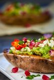 Healthy dinner - Baked sweet potatoes served with guacamole, feta cheese and pomegranate Royalty Free Stock Photos