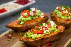 Healthy dinner - Baked sweet potatoes served with guacamole, feta cheese and pomegranate. On the wooden cutting board royalty free stock photos