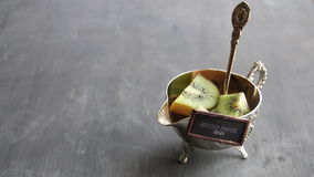 Healthy dinner ideas tag and Kiwi fruit on silver bowl. Food background. stock footage