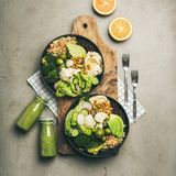 Flat-lay of healthy lunch with superbowls on board and smoothies. Healthy dinner, lunch setting. Flat-lay of vegan superbowls or Buddha bowls with hummus royalty free stock photography
