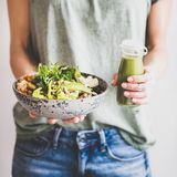 Woman in jeans holding healthy superbowl and smoothie, square crop. Healthy dinner or lunch. Woman in t-shirt and jeans standing and holding vegan superbowl or stock photos